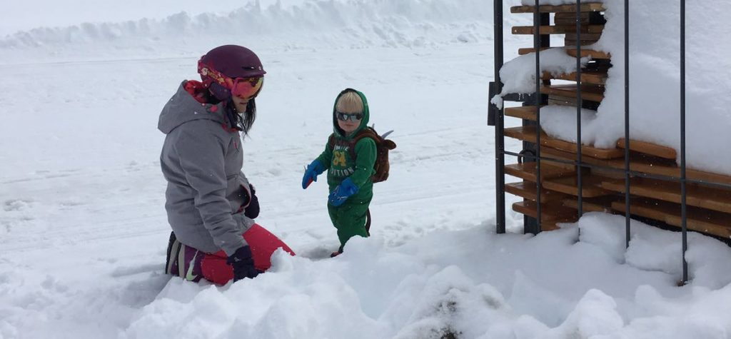Mother and son in snow on their first ski holiday.